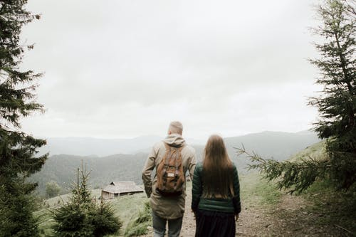 Couple Standing On Mountain Watching The Scenery