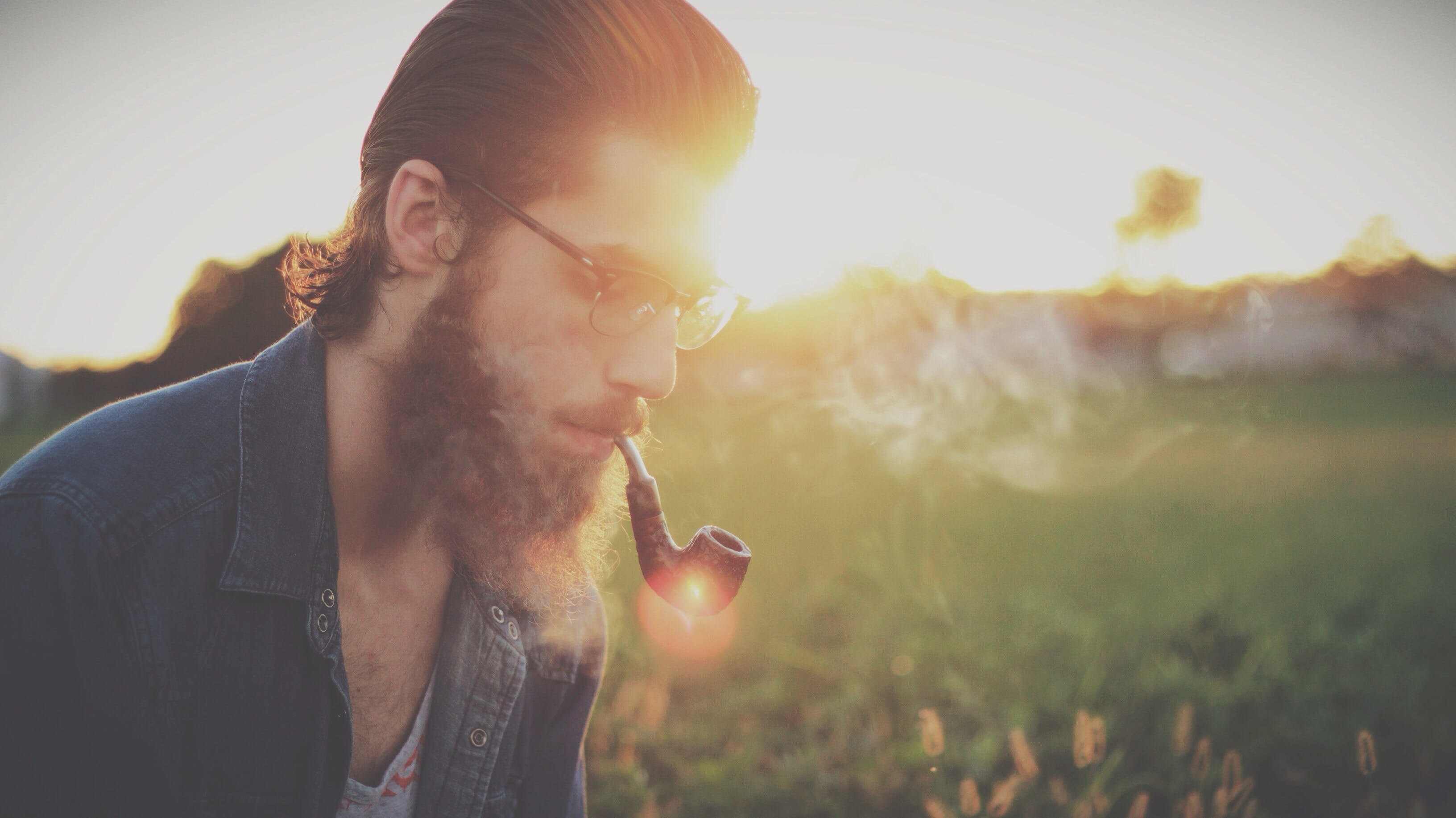 Selective Focus Photography of Man Smoking Using Tobacco Pipe
