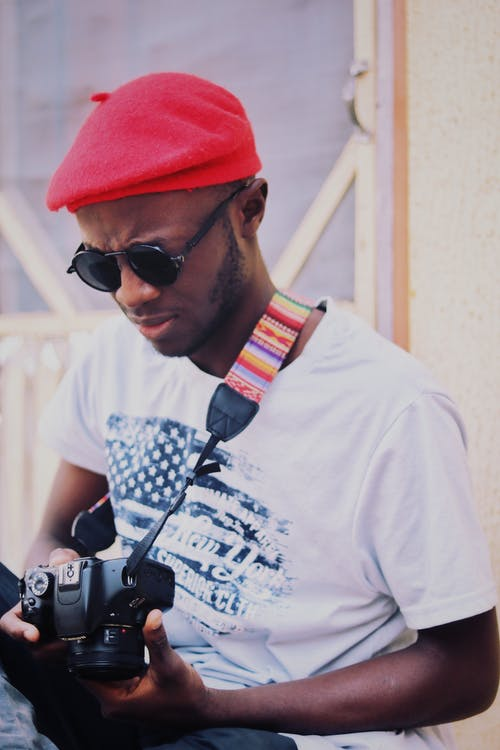 Concentrated young black male traveler in trendy hat and sunglasses setting up photo camera while standing near aged house on street