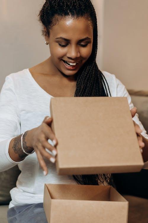 Woman in White Long Sleeve Shirt Holding Brown Cardboard Box