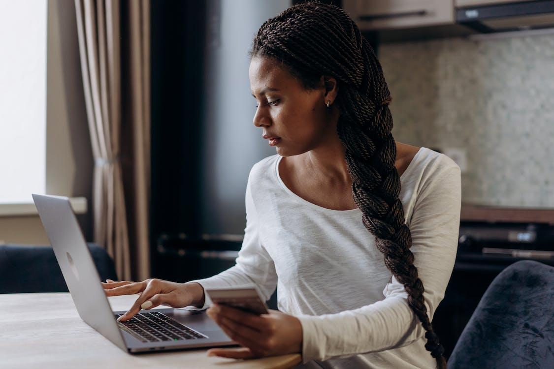 Woman in White Long Sleeve Shirt Using Macbook Pro