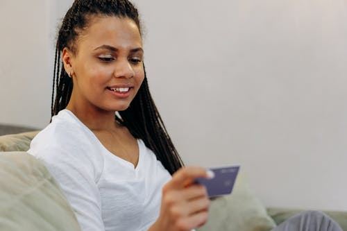 Smiling Woman in White V Neck Shirt Holding Black Smartphone