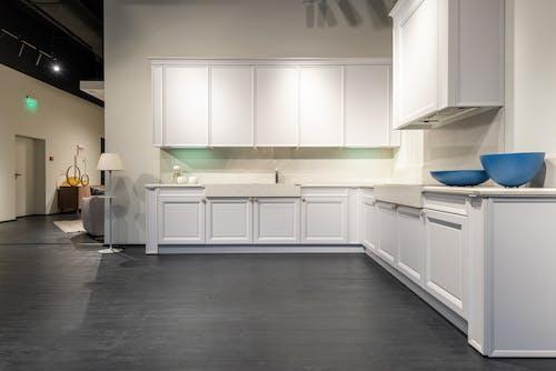 Modern white kitchen units in spacious showroom