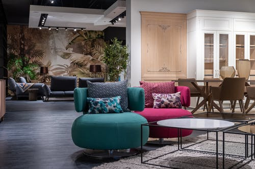 Contemporary trendy interior design of living room with multicolored soft chairs represented in furniture showroom