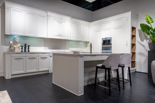 Trendy interior design of modern kitchen with white furniture and built in appliances