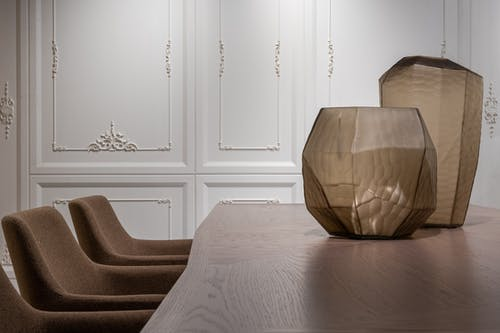 Creative vases placed on dining table in modern apartment