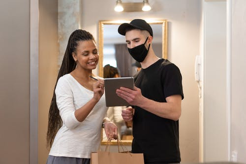 Man in Black T-Shirt Holding Paper for Woman to Sign for Food Delivery