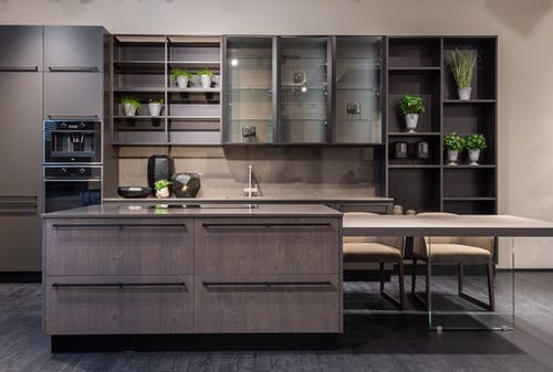 Contemporary kitchen interior design with empty dark furniture and decorative vases and plants