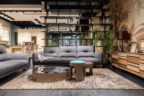 Fancy living room interior design with comfy gray couches creative coffee tables and shelves in spacious contemporary apartment