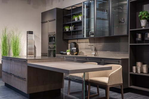 Modern trendy kitchen interior with dark cabinets and counter in spacious contemporary flat