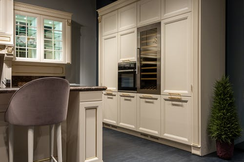 Trendy interior design of modern kitchen with white classy cupboard and cozy high chair in contemporary apartment