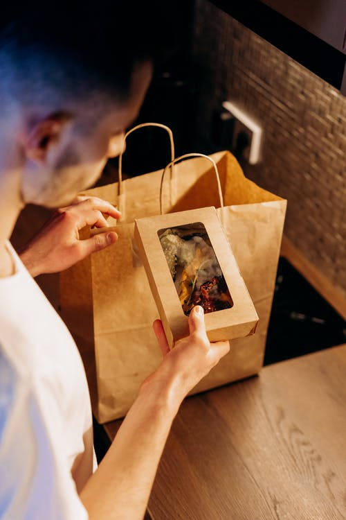 Man Holding Small Box with Food