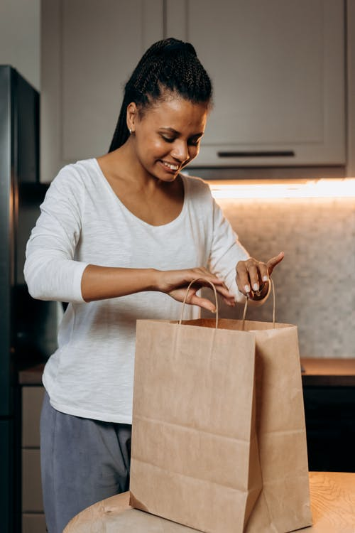 Woman in White Scoop Neck Long Sleeve Shirt Holding Brown Paper Bag