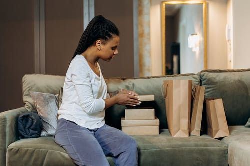 Woman in White Dress Shirt and Blue Denim Jeans Sitting on Gray Couch