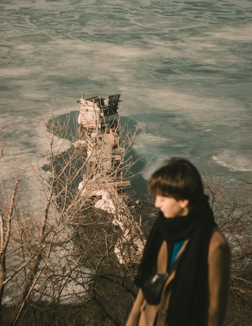 High angle of female standing near leafless bushes against lighthouse and waving sea