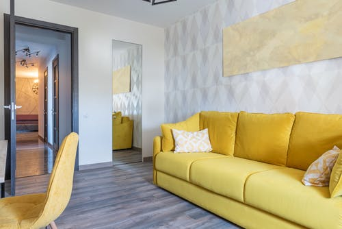 Contemporary room interior with sofa against mirror at home