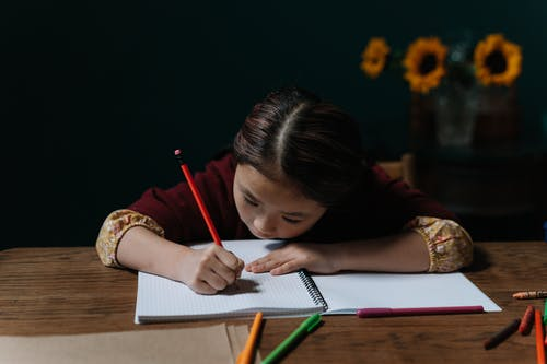 A Girl Writing on a Notebook Using a Pencil