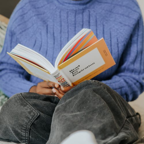 Person in Blue Sweater Reading Book