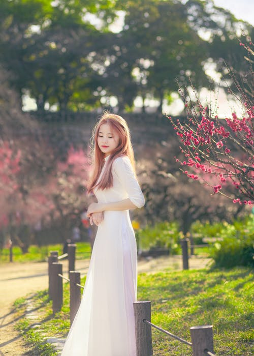 Woman in White Dress Standing Beside Small Fences