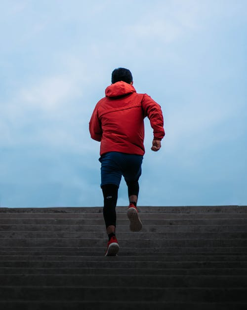 Man in Red Hoodie and Black Shorts Jumping on Brown Wooden Dock