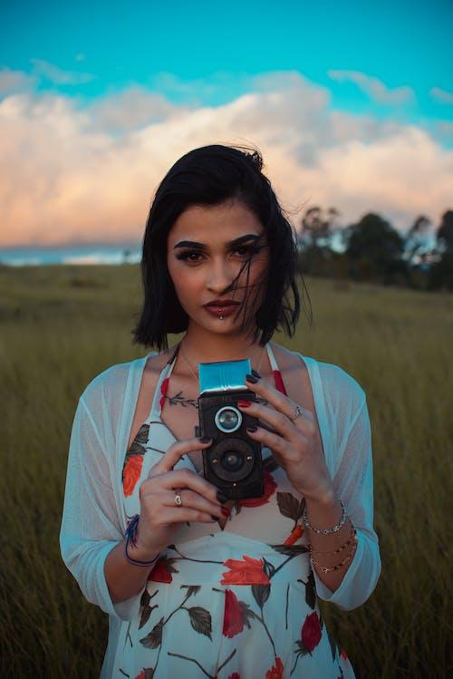 Ethnic woman with retro camera in field
