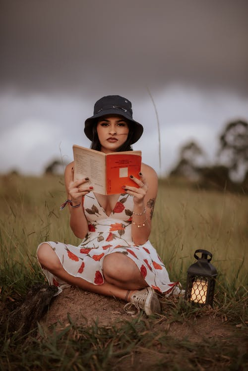 Dull body of serious ethnic female wearing hat and dress looking at camera while sitting on boulder with book and retro lantern against overcast sky on blurred background