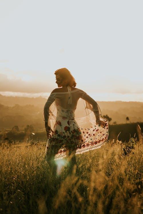 Anonymous woman in summer dress in field