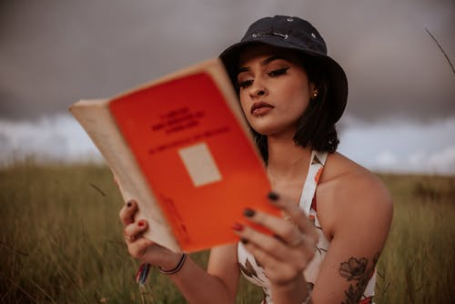 Ethnic woman reading book in nature