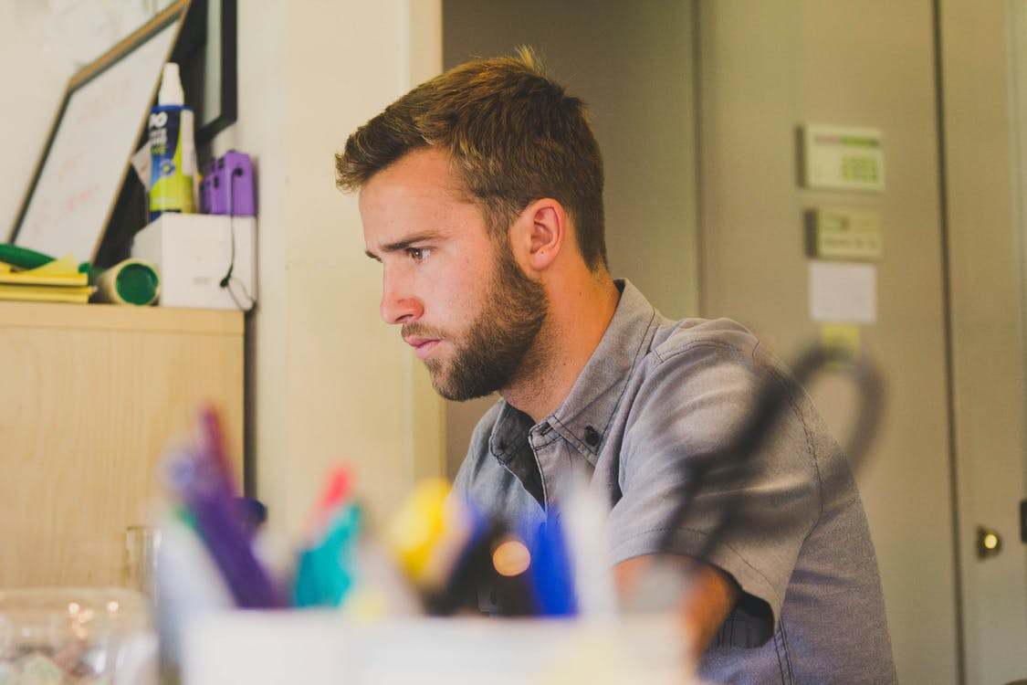 Selective Focus Photography of Man Sitting Near Desk