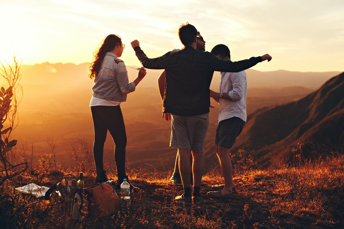 Four Person Standing at Top of Grassy Mountain | Millennial Hospitality Customer Service.