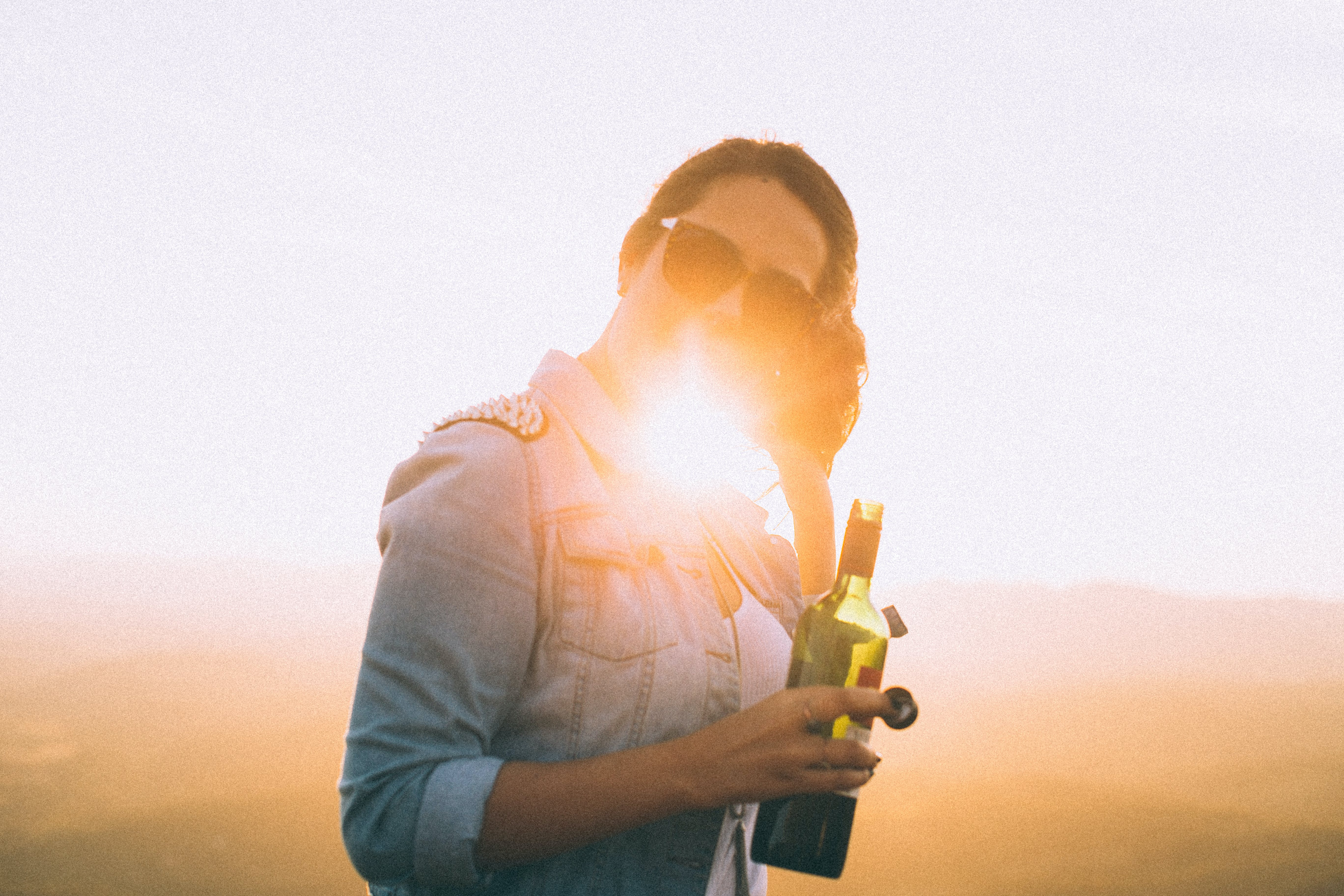 Woman Wearing Blue Denim Jacket Holding Wine Bottle in Golden Hour Photo