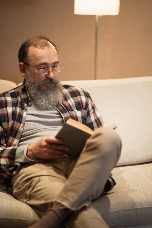 Bearded Elderly Man Sitting on a Sofa while Reading a Book