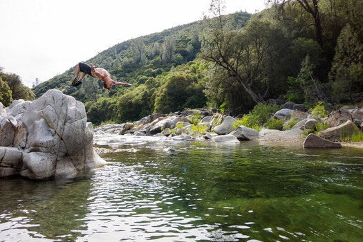 Man in Black Shorts Back Flipping Into River during Daytime