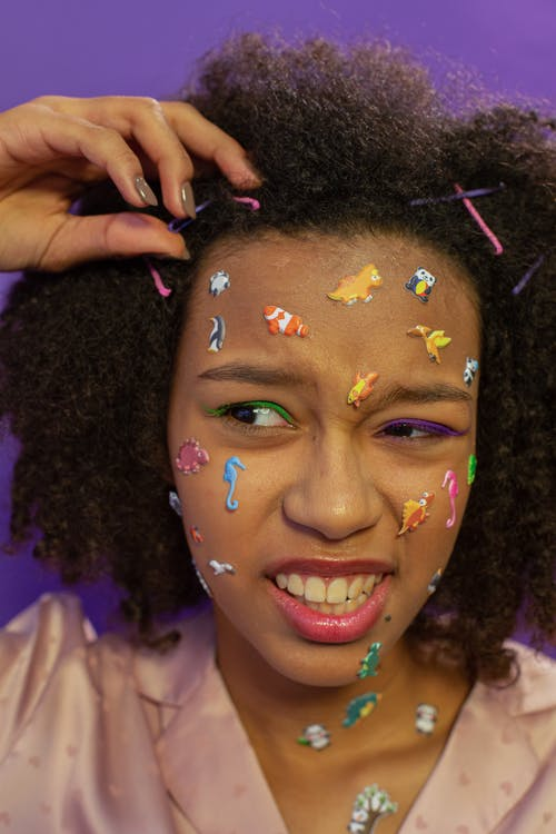 African American female teenager in pajama with various colorful animal stickers on face and hairpins in curly hair and makeup on purple background in light studio