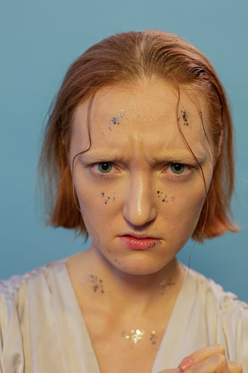 Angry female with shining glitters on face