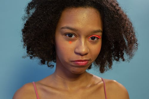 Pensive African American teenager with colorful eyeshadows and small dot on face looking at camera on blue background in light studio