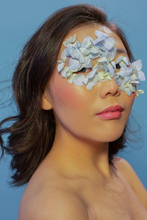 Serious young Asian woman with bare shoulders and blue flowers petals on face with makeup looking at camera in bight studio on blue background