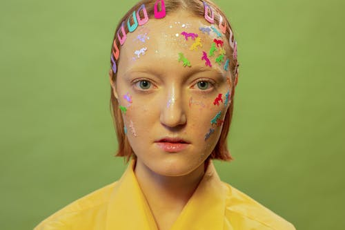 Female with stickers and glitter on face with hairpins