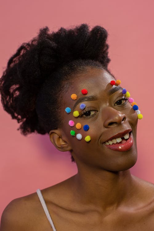 Happy young black lady with colorful pompoms on face in pink studio