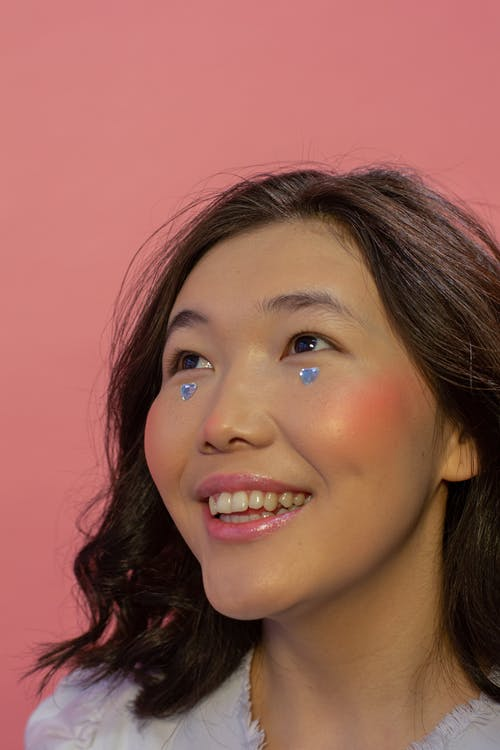 Joyful young Asian lady with perfect skin and gems on face smiling and looking up against pink background