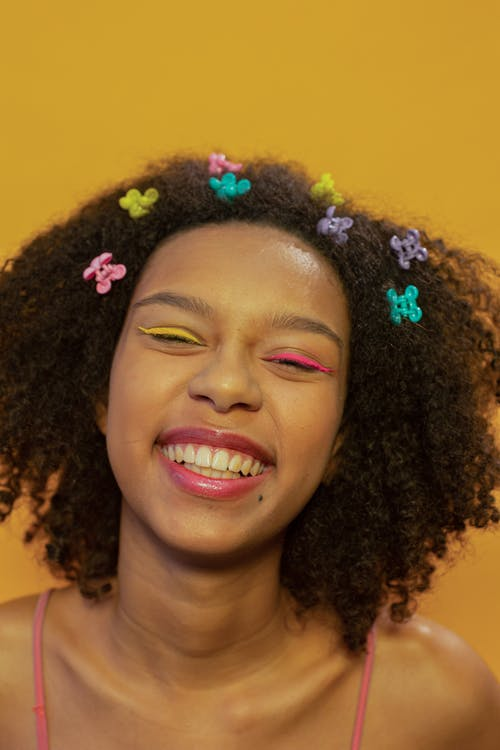 Delighted ethnic female teenager with colorful makeup and mini claws in dark Afro hair smiling happily against yellow background