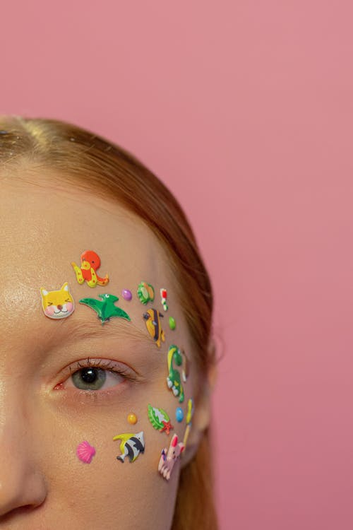 Crop redhead woman with childish stickers on face