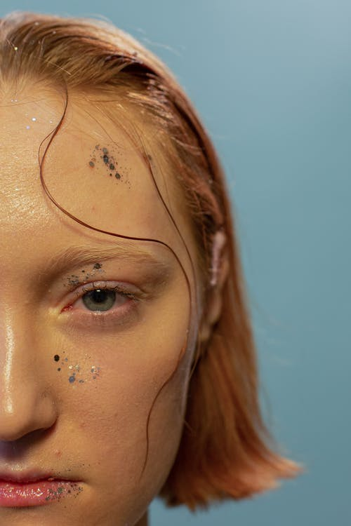 Crop unemotional woman with glitters on face