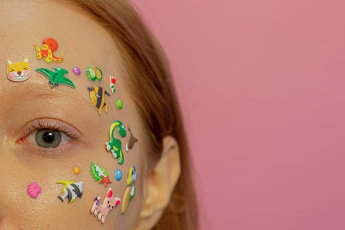 Half face of crop redhead female with blue eyes and multicolored stickers on face against pink background