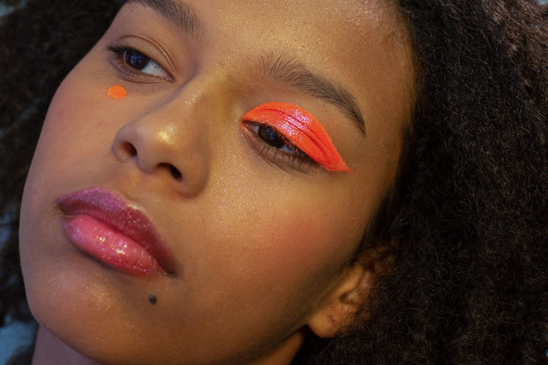 Crop young pensive black female model with bright creative makeup and dark Afro hair looking away in studio