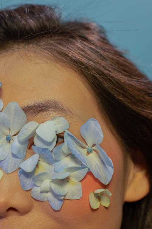 Crop anonymous woman with delicate flower petals on eyes in blue studio