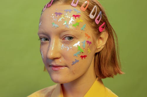 Crop woman with multicolored stickers on face in photo studio