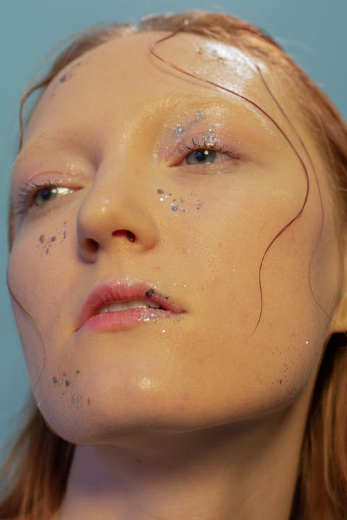 Emotionless female model with glitters and wet hair on face