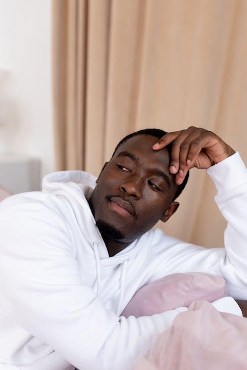 Pensive black man sitting in living room