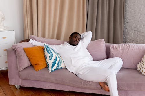 Tranquil African American male in white outfit sitting on pink comfortable sofa in living room and looking at camera